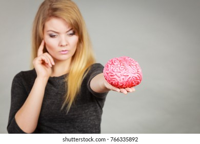 Intellectual expressions, being focused concept. Closeup of attractive woman thinking face expression holding brain