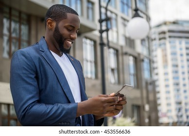 Intelligent African man using telephone outdoors