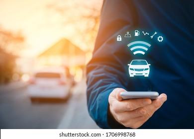 Intelligente Auto-App zum Smartphone-Konzept, Konzept für intelligente Fahrzeuge und intelligente Autos. Person mit Smartphone auf der Straße, Auto im Hintergrund und Wireless-Kommunikation mit dem Auto.