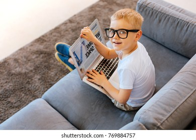 Intelligent child. Joyful nice smart boy holding a laptop and looking at you while reading the article
