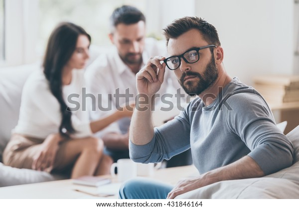 Intelligent and confident. Confident mature man holding looking over shoulder and adjusting his glasses while another man and woman sitting in the background