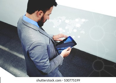 Intelligent and confidents businessman holding touch pad with infographics world map design elements. Young male skilled manager in corporate suit using digital tablet in modern office interior