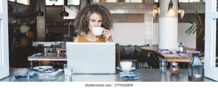 Intelligent curly woman in city cafe, with cup of coffee and latop, working with computer