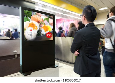 Intelligent Digital Signage , Augmented reality marketing and face recognition concept. Interactive artificial intelligence digital advertisement sushi Japanese restaurant in subway or sky train.