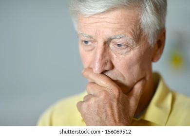 Intelligent elderly man in full vigor thinking on gray background