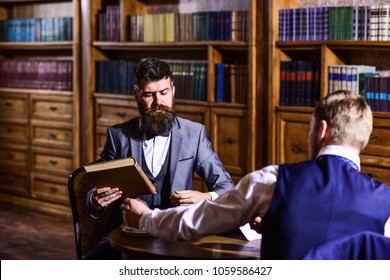 Intelligent elite and scientific people concept. Intelligent men, scientists meet in library. Men in suit with vintage bookshelves on background. Professors speaking about books in antique interior.