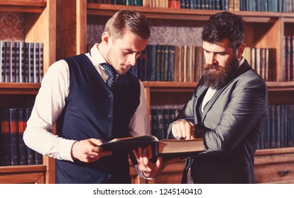 Intelligent elite and scientific people concept. Professors read book in antique interior. Intelligent men, scientists meet in library. Men in suit with vintage bookshelves on background.