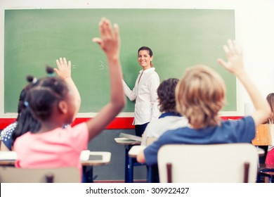 Intelligent group of young school children all raising their hands in the air to answer a question posed by the female teacher, view from behind. Success concept