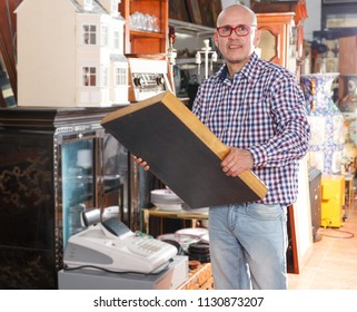 Intelligent mature male chooses antique paintings in store