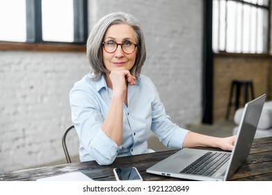 Intelligent mature senior female business owner in glasses with hand on a chin looking at the camera, sitting at the desk in front of laptop. A successful businesswoman enjoying and loving her job