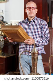 Intelligent middle aged male choosing for retro handicrafts in antique store