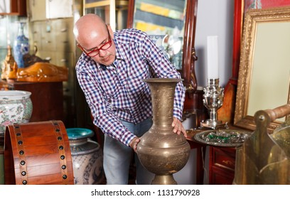 Intelligent middle aged man looking for retro jug in antique store