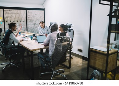 Intelligent multicultural people cooperating on ideas for financial strategy of company during brainstorming meeting in conference room, serious partners sitting at desktop and consultancy together