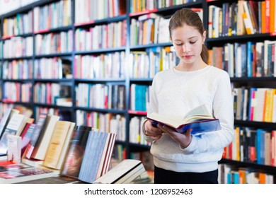 Intelligent  positive smiling preteen girl standing alone near bookcase in library browsing textbooks
