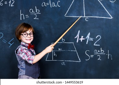 Intelligent smart schoolboy with eye glasses and wooden teacher pointer staying opposite school chalkboard during elementary mathematic lesson at school. Back to school, ready to study concept