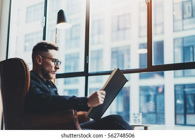 Intelligent stylish businessman reading black book while sitting in vintage chair at his modern office.Young man relaxing after work day.Panoramic windows on blurred background.Horizontal,film effect
