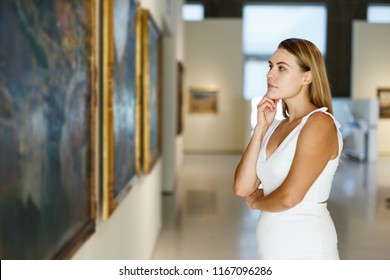 Intelligent young woman holding brochure with exhibition program near paintings in modern museum