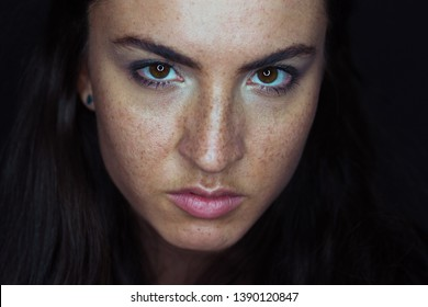 Intense beautiful woman close up portrait against black background. Angry exprssion.