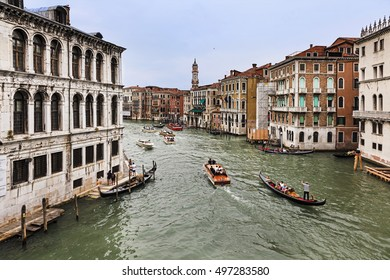 Intense boat and gondola traffic on grand canal in Venice, Italy. Popular city waterway seen from Rialto bridge surrounded by historic palaces and houses.