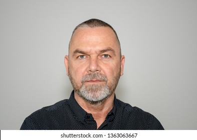 Intense determined bearded middle-aged man staring at the camera with a resolute grim expression over a grey studio background