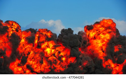 Intense explosion with fire and black smoke and sky in the background