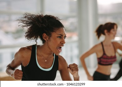 Intense fitness training in gym. Woman working out with full strength in class at health club.