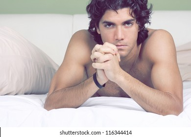Intense gaze at the camera from handsome and sexy guy lying on sheets