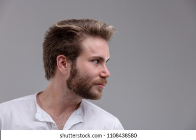 Intense handsome young bearded man looking to the right side of the frame with a serious thoughtful expression and copy space over grey