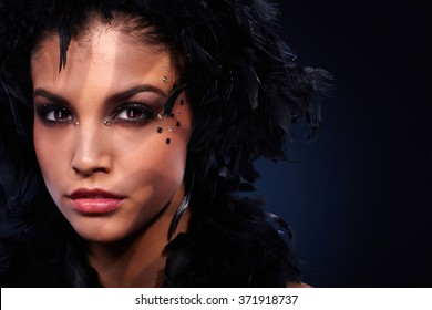 Intense look of beautiful woman wearing party makeup and black feather boa, stripes of shadow and light.