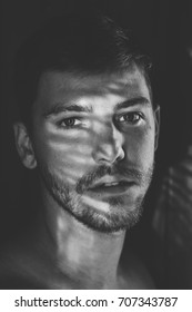 Intense Male Model Head Shot Posing in Shadows in Black and White