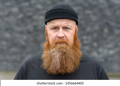 Intense man with bushy red beard wearing a beanie hat scowling at the camera with a penetrating stare over grey