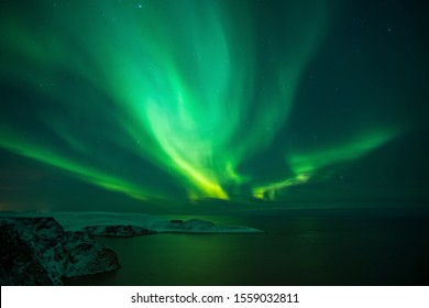 Intense northern lights, Aurora Borealis over Knivskjelloden Island, view from Nordkapp, North Cape, the most northern point of Europe, Finnmark, Norway