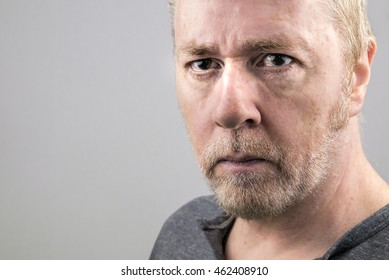 Intense serious tough-looking middle-aged man with stubble and piercing eyes.