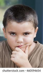 intense seven year old  boy looking at camera