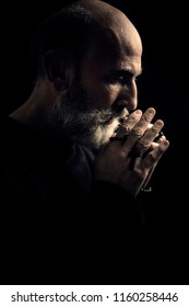 An intense side shot of an old man, praying God with a rosary in his wrinkled hands, semi-silhouette. Ascetic and austere figure.
