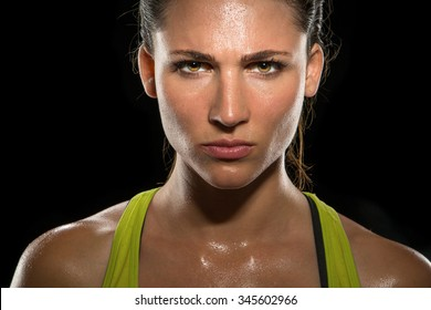 Intense stare eyes determined athlete champion glare head shot sweaty confident woman female powerful fighter close up