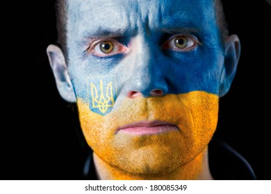 An intense stare from a man with their face painted with the Ukrainian flag.