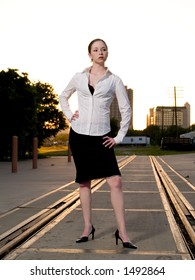 An intense woman in stylish clothes poses on train tracks.