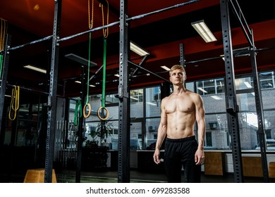 intense workout in dark gym: closeup shot of ripped male torso with defined muscle pattern on chest and arms during gymnastic Bar exercises