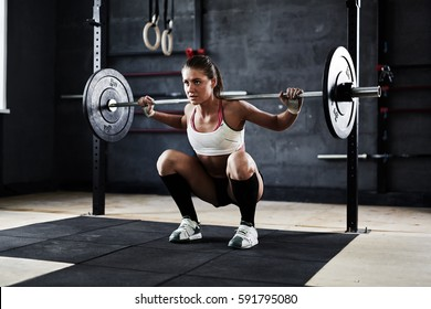 Intense workout in dark gym: strained young sportswoman ready to perform shoulder press exercise with heavy barbell