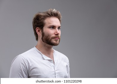 Intense young man staring straight ahead towards the right of the frame with a deadpan enigmatic expression isolated on grey with copy space