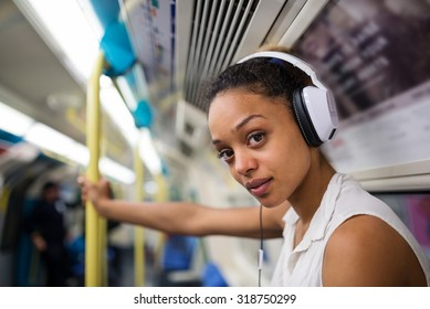 Intense young woman portrait inside underground in London listening to music with earphones.