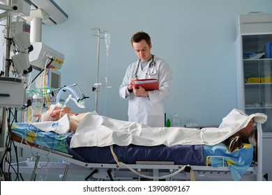 Intensive care caucasian doctor examines intubated critical stance patient writing notes to case report in intensive care department. Doctor working at the hospital.