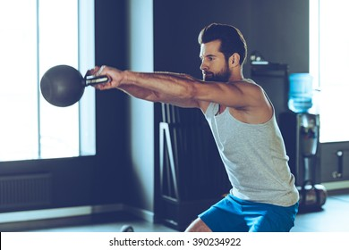Intensive cross training. Side view of young handsome man in sportswear working out with kettle bell at gym