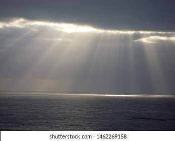 Intensive sun rays falling on Atlantic Ocean from a crack in cloudy sky. Tenerife, Canary Islands.