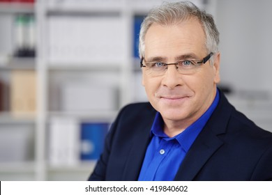 Intent middle-aged businessman wearing glasses looking directly at the lens with a quiet friendly smile, copy space