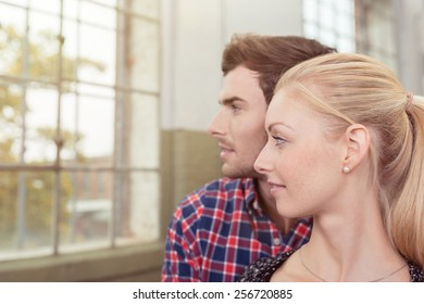 Intent young couple watching through a window as they stand side by side in profile with serious expression, head and shoulders view
