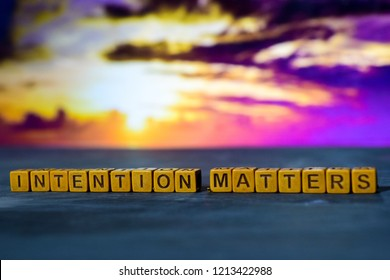 Intention matters on wooden blocks. Cross processed image with bokeh background
