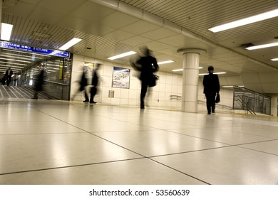 intentional blur of business people rushing in a subway station