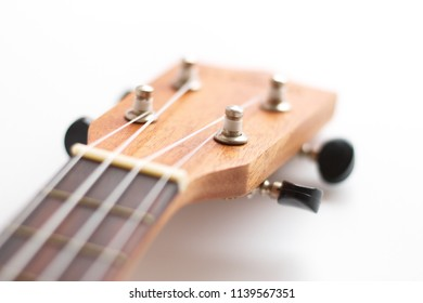 Intentional blurring iamge of head of ukulele showing frets, nut, and tuning keys over a white background. The instrument generally employs four nylon or gut strings.
